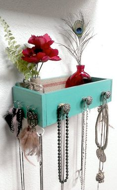 Use and old dresser drawer and add some hooks and knobs to create a shelf/jewelry rack!!