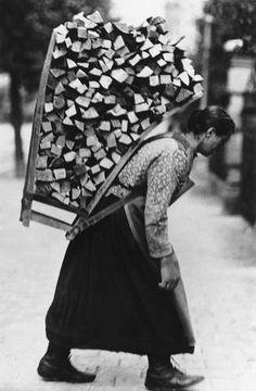 Woman carrying a large load of firewood, date and place unknown