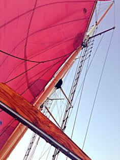 photo by:Lucy tomforde  sailing ship in the Caribbean with a red sail and wood.