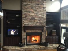 Fireplace Remodel with black bookcases @Tracy DeLeon is this what you were looking for only with tile instead of stone?