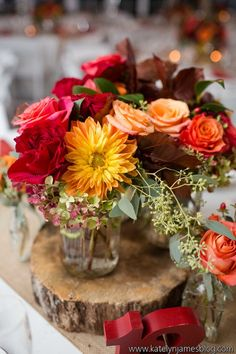 Rustic, fall wedding centerpiece - tree slice #centerpiece with red + peach floral arrangement {Holly Heider Chapple Flowers Ltd.}