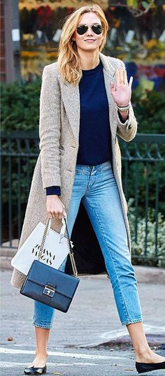 Karlie Kloss in skinny ankle jeans, a navy sweater, long camel coat, black Dolce & Gabbana bag and flats