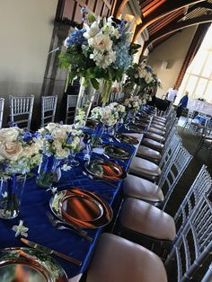 Head table with tall centerpieces in blue, white and silver accents. Hydrangea, peonies, dendrobium orchids, roses, & asiatic lilies