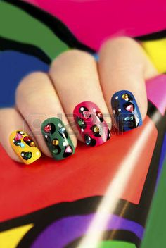 Colorful manicure on nails with rhinestones and design points.