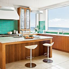 It's hard to compete with an ocean view, but the glass subway tile backsplash in this kitchen does a great job of mirroring the water and laid-back-cool indoors | Coastalliving.com
