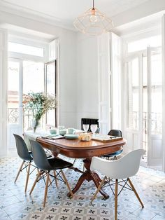 Mix of old and new. Patterned tile, antique table, modern chairs.