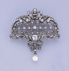 AN ANTIQUE DIAMOND AND PEARL BROOCH   Of openwork design, the central diamond lattice within scroll and foliate surround to the fleur-de-lis surmount and suspended diamond bow and detachable pearl pendant, pearl weighing 27.09 grains (6.77 carats), mounted in silver and gold, circa 1890, with French assay marks for gold