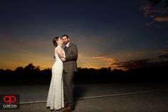 Elizabeth + Patrick's wedding at Lenora's Legacy. Photo credit: Cureton Photography. Bride kissing groom at sunset.