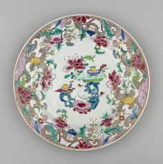A Chinese famille rose porcelain plate, painted at the centre w 2 rocks, one bearing a bowl of fruit, the other 2 small vessels & perched between is a white ibis? Scrolling brown spiral ground rim entwined w pink, yellow & blue flowers.
