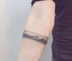 Hand poked landscape forearm band.