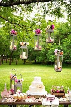 Little candle cages hang over this cake table with pops of pink and a dessert table to envy - love this outdoor cake table set up - Indian wedding decor ideas - modern Indian wedding - pink champagne - cupcakes - floral three tier cake #thecrimsonbride
