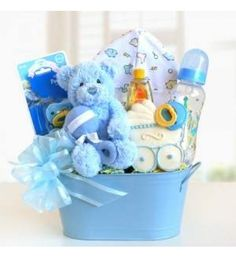 Cuddly Welcome for Baby Boy  An adorable plush and cuddly blue bear with a rattle sits atop our blue keepsake tin, along with a decorated baby bottle, set of two pacifiers, soft cotton cap for baby, baby shampoo and delicious chocolate chip cookies for Mom.