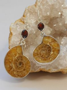 "Ammonite fossils and sparkling faceted oval Garnet gemstones embellish these drop earrings, bezel-set in 925-hallmarked sterling silver. Total length: 2"" Width: .75"""