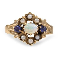 The Cherish Ring. This captivating 10K rose gold Victorian piece features an exceptional horizontally set oval-shaped opal surrounded by six seed pearl accents and two round natural sapphires. Delicate hand engravings add to the lovely floral-inspired design