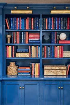 """Lacquered blue bookcases stretch across a single wall in the media room, giving the subterranean seating area the tucked-away feel of a cozy €""""and well-appointed €""""library."""