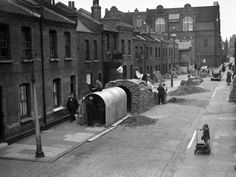 Workmen erect Anderson war shelters in the road outside houses that have no gardens, in East London, England, on Sept. 12, 1939.