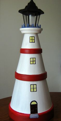 My version of the flowerpot lighthouse. The light on the top is a solar garden light. I used plastic canvas to make the fence around the top.
