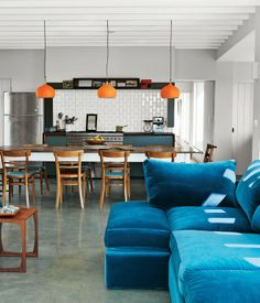 A velvet teal sofa that will look good anywhere. Combined with orange kitchen lamps and a clean-lined kitchen