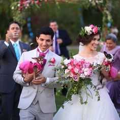 Courtesy picture from Floreria Casablanca Decoracion. The Bride and Groom ready to yes at the church ceremony with their puppies.   Bride head flower arrangement with pink and purple roses. Gorgeous Bouquet with Pink two Colour Roses and Purple.