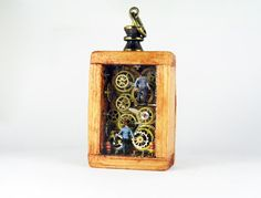 Miniature steampunk pendant factory in small wooden box with tiny people, very intricate and detailed