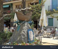 Calella, Spain - July Mini-Ship Mounted On A Pedestal In A Street Of Calella. City On The Costa Brava - A Popular Holiday Destination… All European Countries, Popular Holiday Destinations, July 11, Pedestal, Costa, Photo Editing, Spain, Royalty Free Stock Photos, Table Decorations
