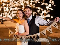 Bride and groom holding a burlap thank you banner for personalized cards. Photo by: FRP