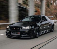 Gorgeous Black Nissan Skyline R34 GT-R running on road