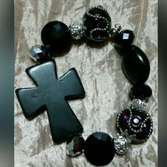 Black cross bracelet Black cross bracelet with black and purple and silver glass beads. This place is very very beautiful .Please feel free to ask any questions before purchasing. And thank you for shopping my closet, custom Jewelry Bracelets