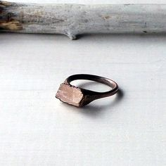 Copper ring features a pale, peach shard of rough morganite. It is a sculptural, gemstone piece that has been electroformed in copper to follow