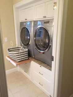 Laundry Room Design. Laundry Room Ideas. Laundry room machine ideas that are easy on your back. Enclosed Washer and Dryer | Laundry room features built-in cabinets encasing a silver front-load washer and dryer accented with pull out trays sandwiched between cabinets above and stacked drawers below. Via Decorpad.