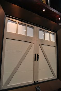 Clopay Coachman Collection steel and composite carriage style garage door. Design 22 with REC13 windows, factory finished in Sandtone with Desert Tan overlays. www.clopay.com