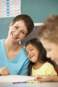 Classroom picture of a young Hispanic girl leaning her head against the shoulder of the woman helping her with schoolwork.