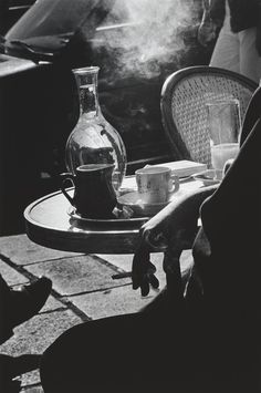 Ralph Gibson Cafe, Paris, 1986 [person smoking in front of table with coffee cup, water glass and jug, and creamer holder upon in, chair in background