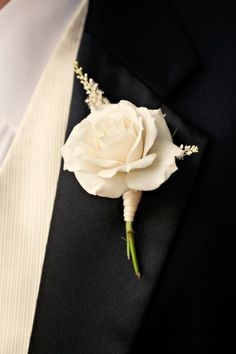 boutonniere - ivory spray rose wrapped in raffia with the stems showing