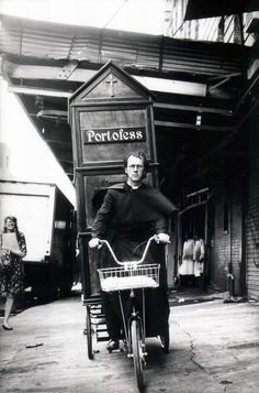 Father Anthony Joseph (aka Joey Skaggs) pedals his Portofess, a portable confessional booth bringing religion on the move to people on the go.