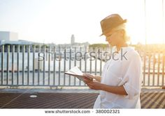 Charming female tourist reading location map while standing on bridge near sea in sunny summer day, young lost woman traveler dressed in stylish hat examines city atlas during adventure tour overseas
