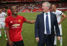 Manager Sir Alex Ferguson of Manchester United '08 XI speaks to Patrice Evra after the Michael Carrick Testimonial match between Manchester United...