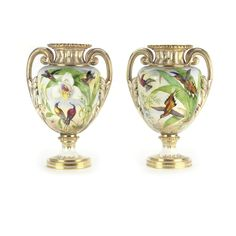 A pair of Coalport two-handled vases circa 1860 each ovoid body well painted with birds amongst trees and flowers beneath a fluted waisted neck enriched in gilding, set with scroll and leaf moulded handles, raised on a circular foot.