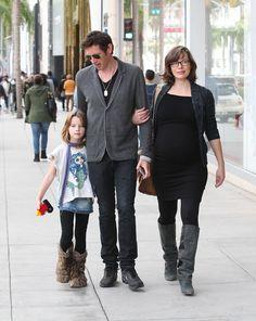 Pregnant Milla Jovovich - black dress, grey shrug, tights, suede knee boots