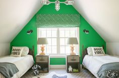 In the boys' room, Lillian August lamps sit on RH nightstands next to a pair of vintage beds with Serena & Lily bedding. A green Lulu DK window treatment echoes the hue of the accent wall, where a pair of sconces from Schoolhouse Electric provide extra lighting.