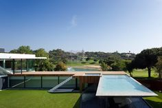 Casa Vale do Lobo, Portugal by Vasco Vieira of Arqui+ Arquitectura.The contemporary home is stark white with a mix of wood and glass. The site of the home is 'U' shaped, one side being the home, on the other a wooded deck to relax on and the infinity pool. Though the golf course property sits on a sea side, this epic pool might be enough to keep it's owners in fresh waters.