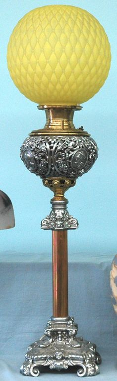 lighting, , A late 19th century, brass, copper and cast white metal Victorian banquet oil lamp, yellow Quilted Satin glass ball [or globe] shaped shade. LAmp consist of a square ornate cast white metal base standing on four scrolled feet, sies of base supports a tall reeded tubular copper shaft ot column surmounted by a cast white metal architectural capital with pierced medallion design brass connector above   Circa 1876-1900