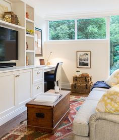 Cozy living room centers on a white built-in media center topped with a large flat screen TV flanked by bookshelves alongside a built-in desk underneath a framed pin board paired with a ivory and navy desk chair.