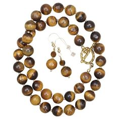 This elegant necklace is crafted by alternating smooth and faceted Tiger's Eye gemstone beads, highlighted and separated by small smooth gold-filled beads. Closure is with a pretty twisted gold-filled Knot Necklace, Jewelry Necklaces, Resin Jewellery, Chunky Jewelry, Antique Jewellery, Jewlery, Beaded Bracelets, Tiger Eye Jewelry, Tigers Eye Necklace