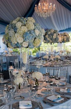 Giant clouds of blue and white hydrangea,white roses,minimal greens with a hanging rose petal drop inside the vase.