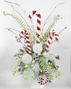 Capture the whimsy and elegance of Christmas with this Candy Cane Centerpiece. Filled with an abundance of special features including: - Candy canes, including one and four and three more g Christmas Flower Arrangements, Christmas Table Centerpieces, Christmas Flowers, Outdoor Christmas Decorations, Christmas Themes, Vintage Christmas, Christmas Wreaths, Christmas Crafts, Christmas Ornaments