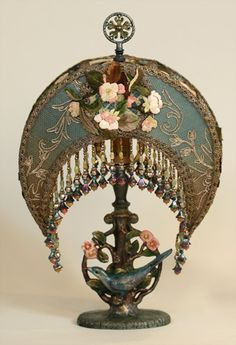 Pair of 1920s metal bluebird and flower hand-painted lamps hold small Crescent Moon shades dyed dusty teal to antique gold. The shade is covered in antique silver metallic netting with a beautiful raised scroll pattern and overlaid with pink and green training flower appliques. The shades are hand-beaded in matching tones and light up beautifully.
