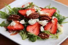 Quick and easy strawberry goat cheese arugula salad recipe made with strawberry slices, crumbled goat cheese, arugula, red onions, spicy pecans, balsamic vinegar and olive oil.