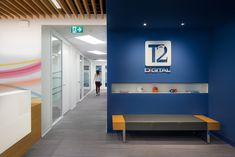 Reception at T2 Digital - office interior design by SSDG Interiors Inc. - wood upholstered bench, reception desk, office design, wood slat ceiling, logo signage, modern office design