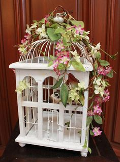 This unique and beautiful white birdcage is made of wood and wire metal. Adorned with silk floral accents; purple violet and lime green flowers, green leaves, and wooden twigs. A faux bird located inside completes the piece. It is perfect for garden themed, whimsical or everyday decor. Approximate Dimensions: Height: 15 Width: 9 Depth: 7 *Please remember that all my items are creatively designed, arranged, and decorated by hand so they are not always perfect in terms of being exactly the…